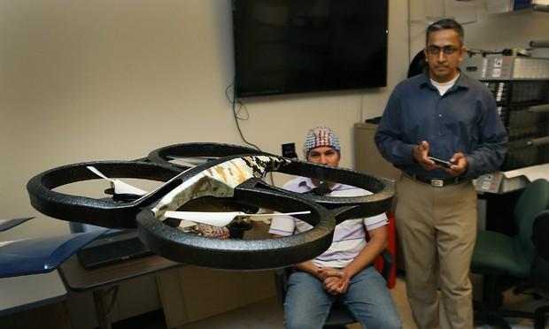 Prasanna Kolar, à direita, usa celular para controlar drone durante pesquisa na Universidade do Texas em San Antonio, nos EUA (Foto: The San Antonio Express-News, Bob Owen/AP)