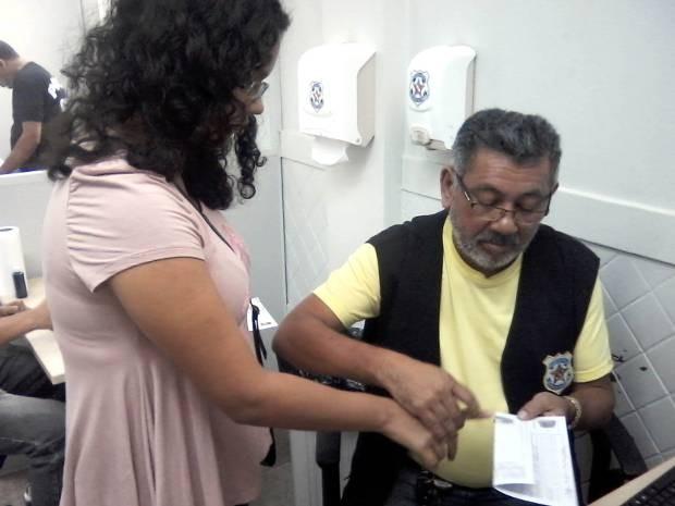 Mulher carimba o polegar em carteira de identidade, durante mutirão realizado no feriado. (Foto: Divulgação/Polícia Civil)