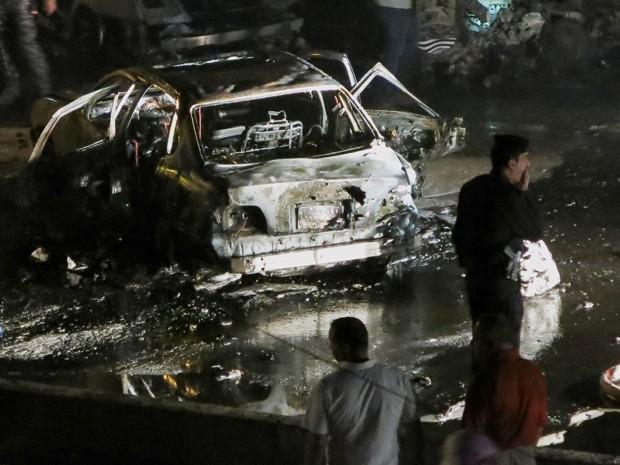 Civis e integrantes de forças de segurança se reúnem ao redor de um carro bomba que explodiu no bairro Mansour, em Bagdá, na segunda-feira (27) (Foto: AP Photo)