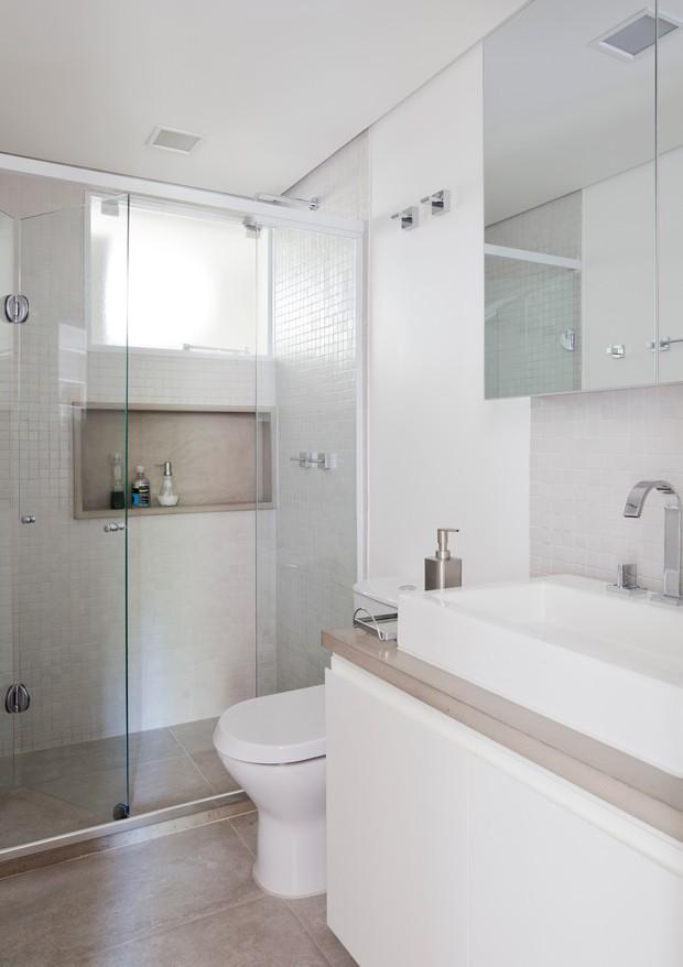O piso do banheiro é o mesmo utilizado na cozinha, porcelanato com aparência de concreto, para dar uniformidade aos espaços. A combinação branco com cinza ganha cor com os objetos de decoração do casal (Foto: Maira Acayaba)