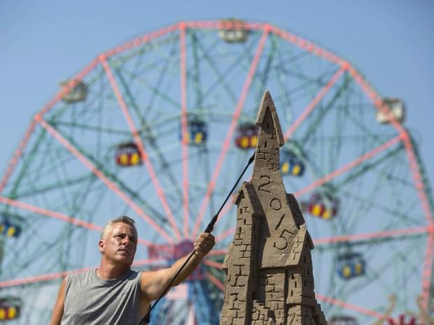 Participante ergue um castelo em concurso de esculturas na areia em Nova York, neste sábado (15) (Foto: Reuters/Andrew Kelly)