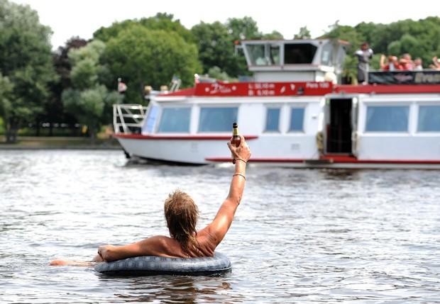 Homem levantou cerveja para 'saudar' embarcação em rio de Berlim, na Alemanha (Foto: Britta Pedersen/AFP)
