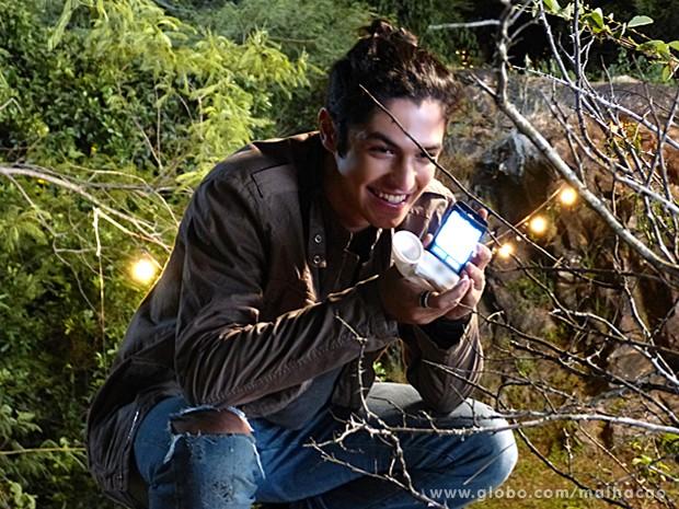Antônio usa um aparelho acoplado ao celular para reproduzir os gritos (Foto: Malhação / TV Globo)