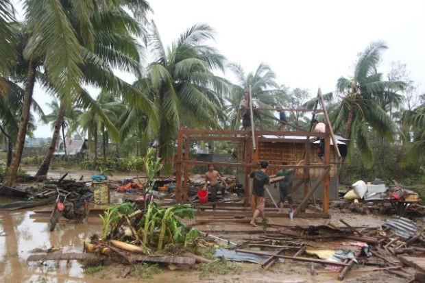Moradores do Vale de Compostela, nas Filipinas, tentam reconstruir uma casa destruída pela passagem do tufão Bopha (Foto: Karlos Manlupig/AP)
