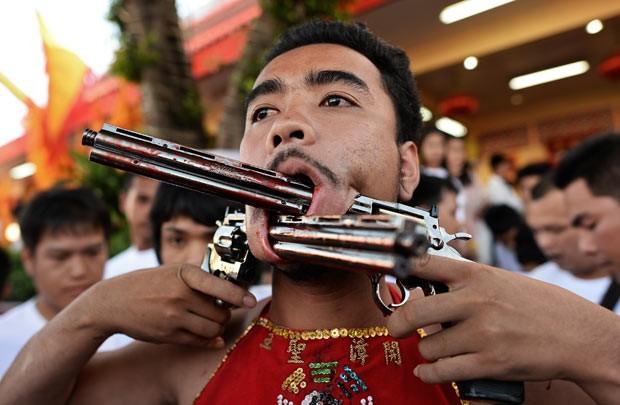 Devotos furam bochechas com metal em ritual de purificação na Tailândia (Foto: Christophe Archambault/AFP)