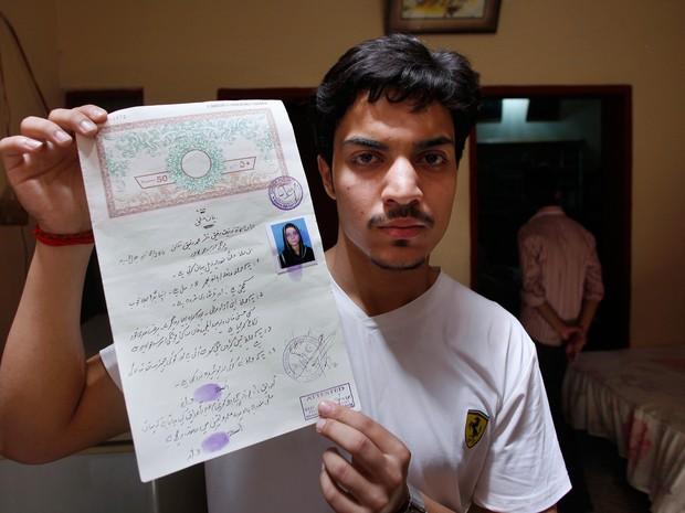 Hassan Khan, marido da vítima, mostra o certificado de casamento (Foto: K.M. Chaudary/AP)