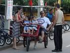 Paulo César Grande anda de triciclo com Claudia Mauro e os filhos, no Rio