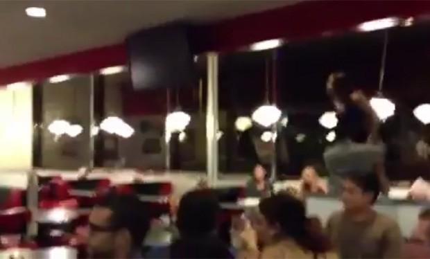 Uma das mulheres subiu em uma mesa do restaurante antes de ser detida por um policial (Foto: Reprodução/Youtube)