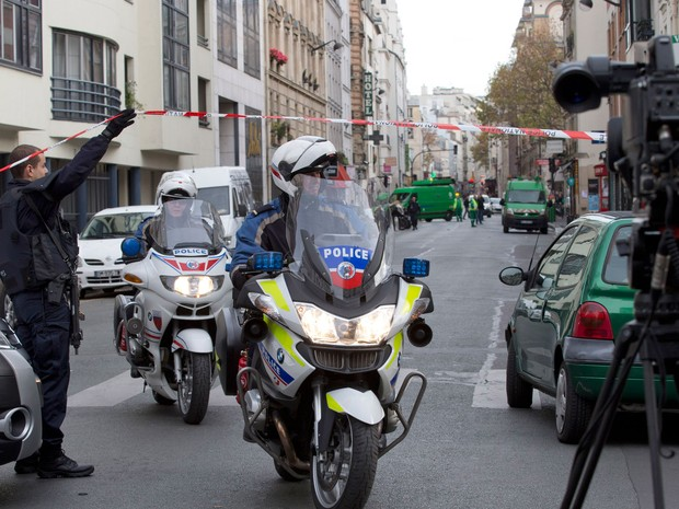 Policiais passam por bloqueio na rua de Charonne, perto do local do tiroteio em  (Foto: AP)
