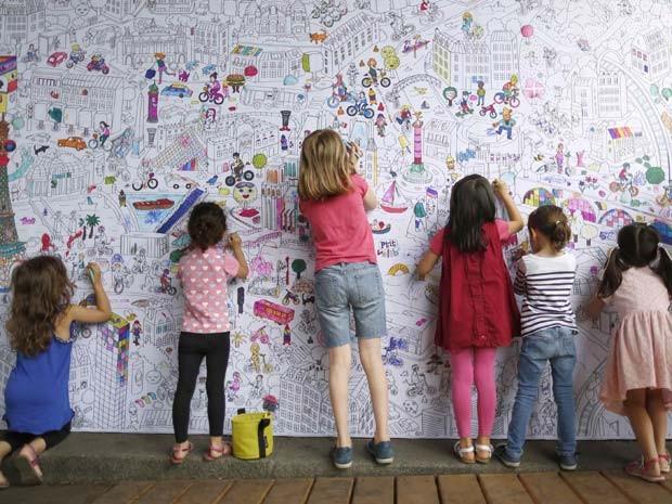 Crianças pintam painel com o mapa de Paris durante inauguração de praia temporária às margens do rio Sena nesta segunda-feira (20) (Foto: REUTERS/Charles Platiau)
