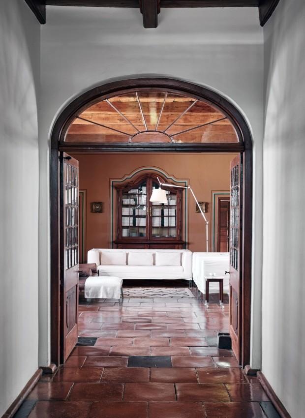 A porta dupla, com seu elegante painel de vidro, abre-se para a sala de estar mobiliada com sofás de Philippe Starck para a Driade e a luminária Tolomeu da Artemide (Foto: Greg Cox / Bureaux)