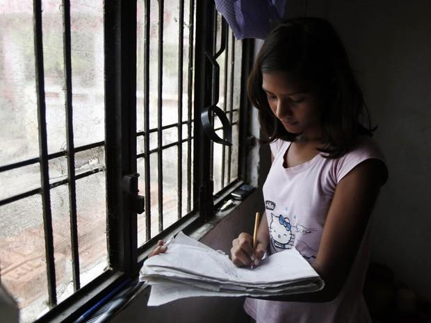 Sushma estuda na janela do apartamento onde mora com a família (Foto: Rajesh Kumar Singh/AP)