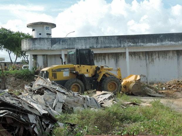 Retroescavadeira retira os entulhos e mato que se acumulam no terreno que fica ao lado do complexo (Foto: Marina Barbosa/G1)