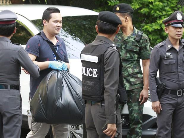 Policiais retiram provas do apartamento onde o suspeito foi preso (Foto: Reuters)