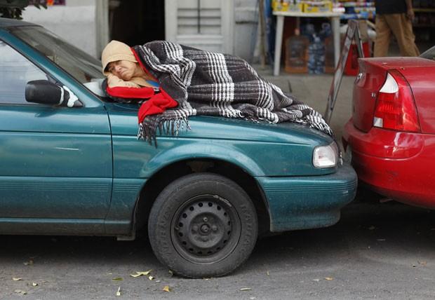 Uma mulher foi fotografada tentando tirar um cochilo sobre o capô de um carro na Cidade do México. A cena foi registrada pelo fotógrafo Tomas Bravo. (Foto: Reuters)