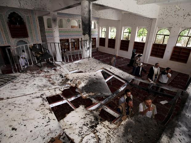 Pessoas observam mesquita destruída em Sanaa, Capital do Iêmen, após atentado suicida que ocorreu na sexta (22). (Foto: Mohamed al-Sayaghi/Reuters)