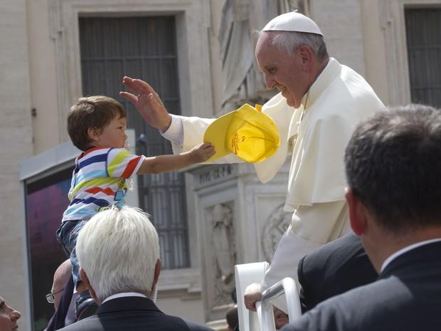 Papa Francisco ganha um boné de uma criança durante audiência geral na Praça de São Pedro, no Vaticano. (Foto: Alessandra Tarantino/AP)