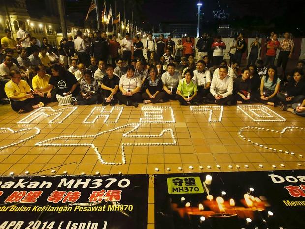 Familiares dos passageiros do voo da Malaysian Airlines acendem velas em vigília para marcar um mês do desaparecimento do avião (Foto: Reuters/Samsul Said )