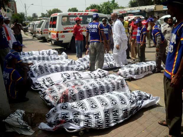 Voluntários ao lado de vítimas da explosão de uma bomba em Karachi. (Foto: Rizwan Tabassum / AFP Photo)