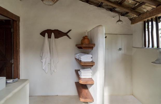 Banheiro | Em vez de armários, apenas prateleiras de cumaru compõem a área. O pendente de bambu foi feito pelos indígenas pataxós e o cabideiro em formato de peixe pelo artesão João Luz Calazans (Foto: Evelyn Müller/Editora Globo)