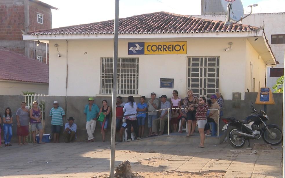 Moradores passam madrugada na fila para sacar dinheiro em Correios (Foto: Damião Tomé / TV Paraíba)