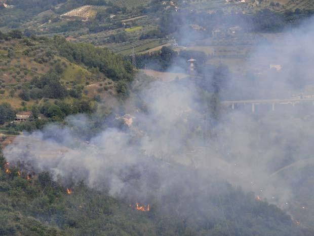 Chamas são vistas em mato depois que dois aviões caça se chocaram nesta terçafeira (19) na Itália (Foto: AP Photo/Sandro Perozzi)