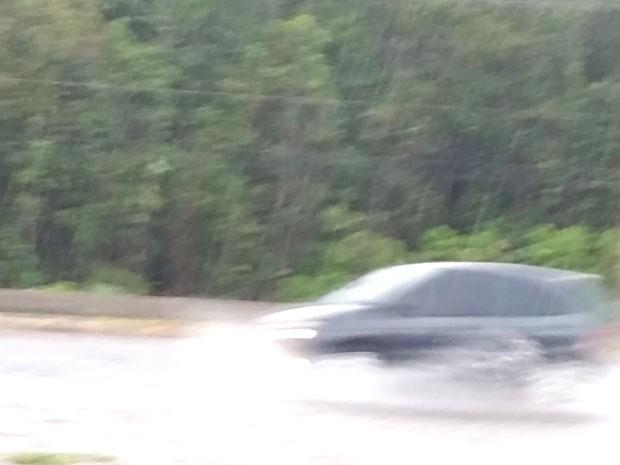 Carro passa sobre área alagada na EPTG, no DF (Foto: G1)