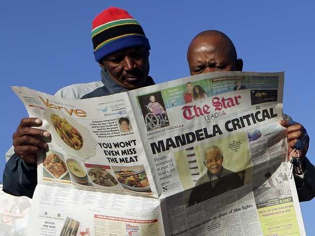 Sul-africanos procuram em um jornal as notícias sobre o estado de saúde de Mandela. (Foto: Siphiwe Sibeko / Reuters)