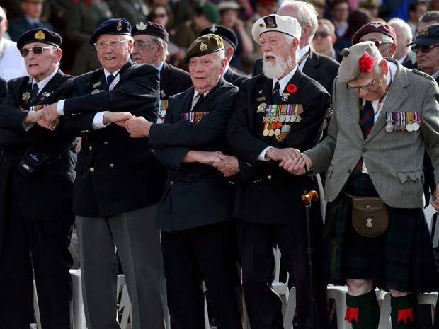 Veteranos da Segunda Guerra Mundial dão as mãos enquanto cantam música durante cerimônia do 70º aniversário do Dia D, nesta sexta-feira (6) (Foto: REUTERS/Leon Neal/Pool)