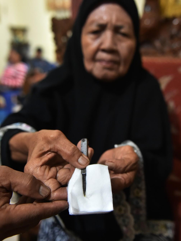 Curandeira mostra ferramenta usada na circuncisão de meninas em Gorontalo, na Indonésia (Foto: Bay Ismoyo/AFP)