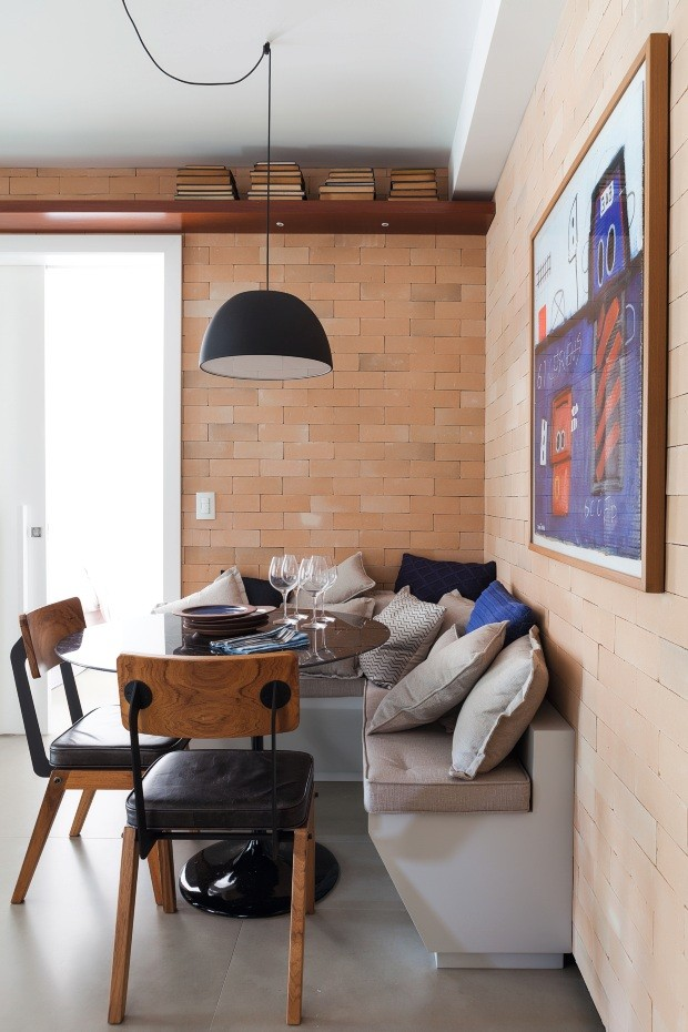 O banco em L, executado pela Colombo Movelaria, tem almofadas e futons de linho da Tapeçaria Conceito. As azuis são da Codex Home. Sobre a mesa Saarinen, pratos da Dpot Objeto. Pendente da Reka. Cadeiras da Prototyp& (Foto: Lufe Gomes / Divulgação)