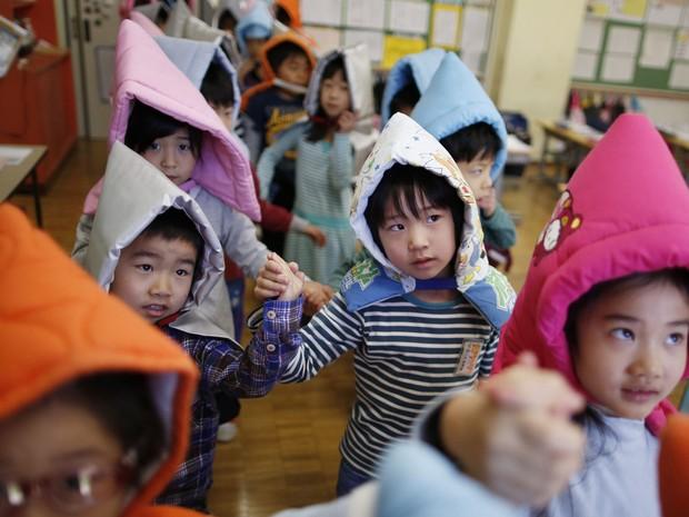 Alunos também colocaram tapetes acolchoados para proteger a cabeça (Foto: Issei Kato/Reuters)