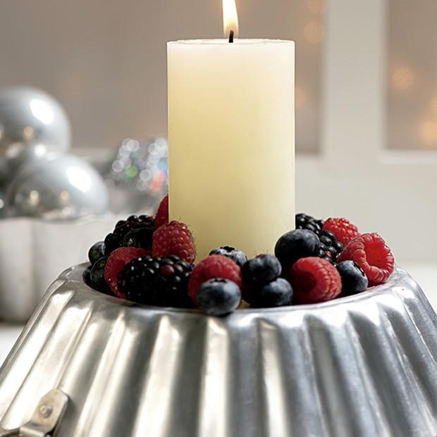 A luz das velas deixa o ambiente aconchegante e intimista. Que tal criar um castiçal que também sirva como arranjo de frutas. Dica: as frutas vermelhas (amora, framboesa e morango) são uma ótima pedida graças ao tamanho e as cores. (Foto: Iara Venanzi/Casa e Comida)