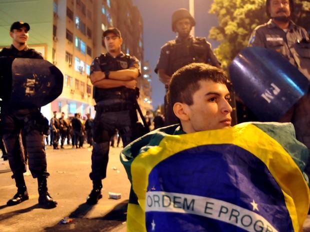Manifestante senta em frente a barreira policial depois dos protestos próximo ao Maracanã (Foto: Luiz Roberto Lima/G1)
