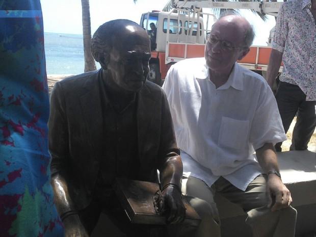 Filho de Aurélio Buarque de Holanda sentado ao lado da estátua do pai (Foto: Larissa Vasconcelos/G1)