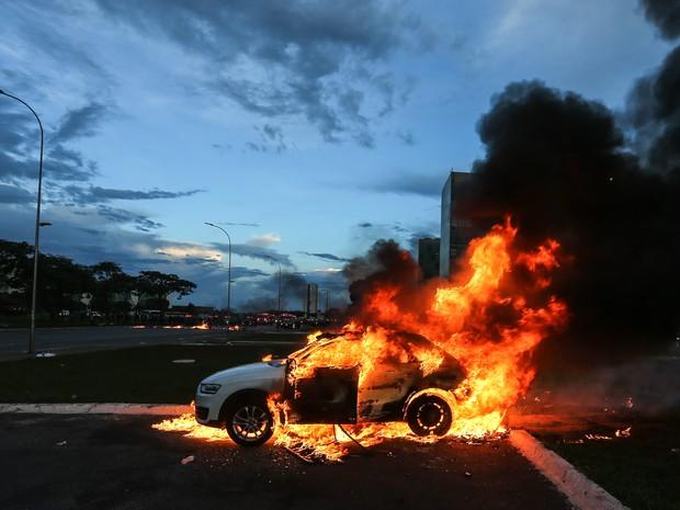 Um carro em chamas é visto durante um protesto na Esplanada dos Ministérios, em Brasília, contra a PEC 55, que limita os gastos públicos para os próximos 20 anos (Foto: Dida Sampaio/Estadão Conteúdo)