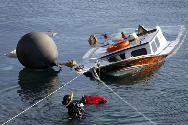 Oficiais da Guarda Costeira grega resgatam corpo após acidente com bote de refugiados perto da ilha de Lesboas (Foto: Giorgos Moutafis/Reuters)