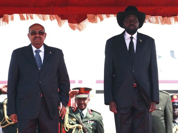 Presidente do Sudão Omar Hassan al-Bashir (à esquerda) e o presidente do Sudão do Sul Salva Kiir  (à direita) escutam seus hinos nacionais na chegada ao aeroporto de Juba nesta sexta-feira (12) (Foto: REUTERS/Andreea Campeanu)