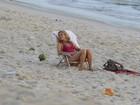 De maiô, Christine Fernandes curte o fim de tarde com o filho na praia