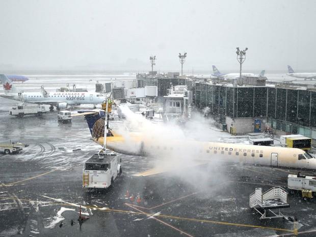Funcionários retiram gelo de avião no aeroporto de LaGuardia, em Nova York. Vários voos foram cancelados por causa da nevasca que atinge a Costa Leste dos EUA. (Foto: AP Photo/Seth Wenig)