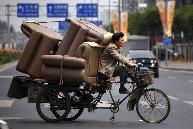 Homem é flagrado dirigindo triciclo superlotado de sofás em rua de Pequim nesta terça-feira (5) (Foto: David Gray/Reuters)