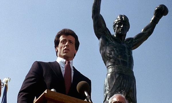 O ator Sylvester Stallone em cena de Rocky III na qual aparece em frente à estátua recém-adquirida por ele (Foto: Reprodução)