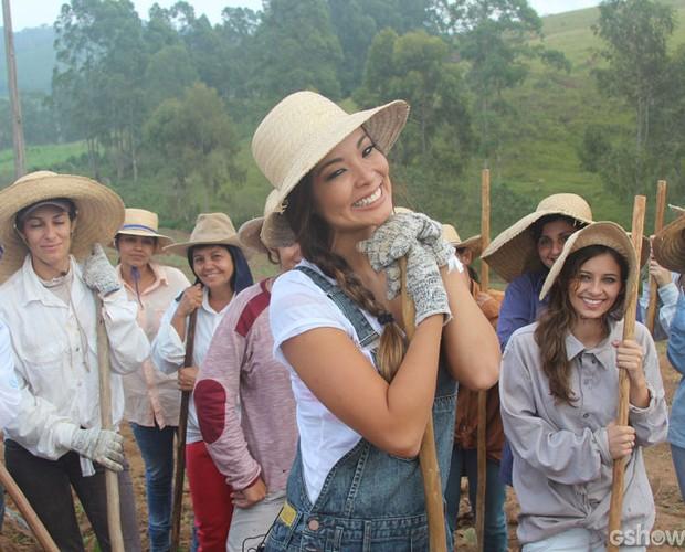 Carol Nakamura posa com mulheres duranten colheita (Foto: TV Globo/ Domingão)