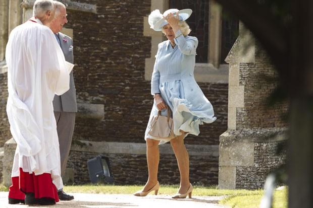 A duquesa da Cornualha, Camilla, segura vestido e chapéu ao chegar para o batizado da princesa Charlotte junto com o marido, o príncipe Charles (Foto: Matt Dunham/AP)
