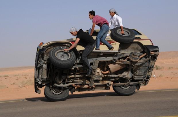 Em manobra perigosa, uma das rodas do carro é retirada durante o percurso (Foto: Mohamed Al Hwait/Reuters)