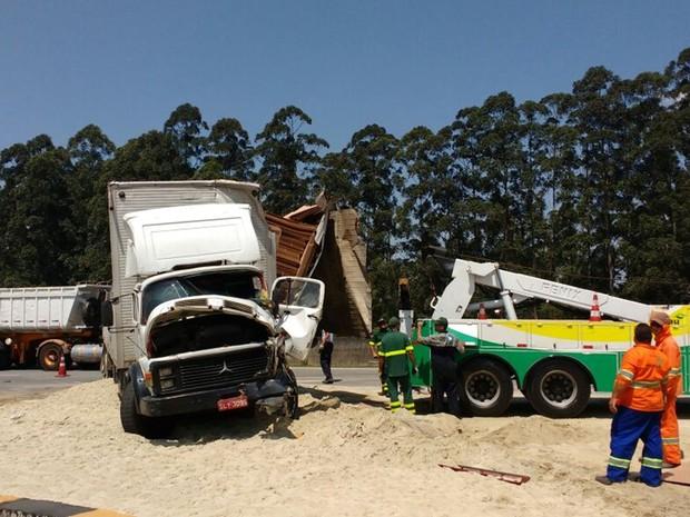Homens trabalham para retirar caminhão na Ayrton Senna, em Itaquaquecetuba (Foto: Sandra Redivo/ TV Diário)