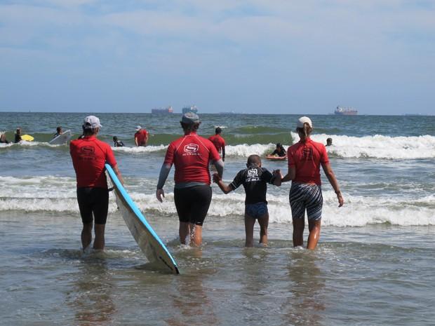 Professores e Rapha entrando no mar para uma aula de surf (Foto: Mariane Rossi/G1)