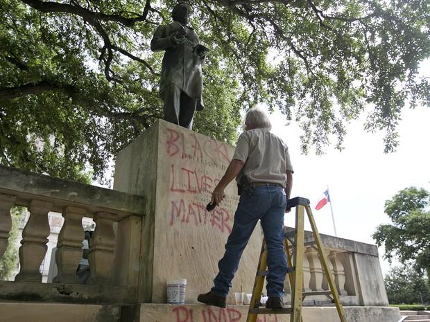 Funcionário limpa pixações na estátua de Jefferson Davis em campus da Universidade do Texas, na terça (23) (Foto: Deborah Cannon/Austin American-Statesman via AP)