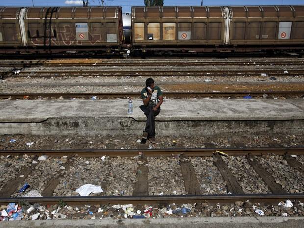 Imigrante fala ao celular enquanto espera trem na Macedônia em direção a Sérvia. Foto de 18 de agosto de 2015 (Foto: Darko Vojinovic/AP)