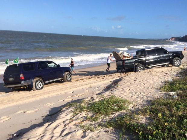Duas caminhonetes invadiram a área destinada para banhistas na Praia do Sol no LItoral Sul da Paraíba, durante este domingo (29). Os veículos ficaram atolados na areia da praia enquanto a maré subia (Foto: Walter Paparazzo/G1)